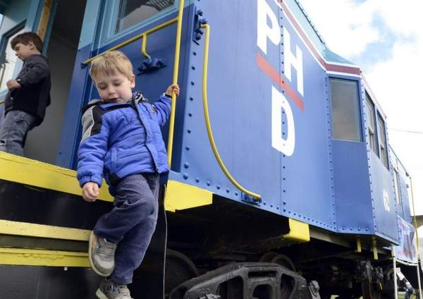 Jake Rescoe, 3, of Clinton Township climbs down the steps of a bay window style caboose painted with the Port Huron & Detroit Railroad logo during a National Train Day event at the former Port Huron and Detroit Railroad yard. / MELISSA WAWZYSKO/TIMES HERALD