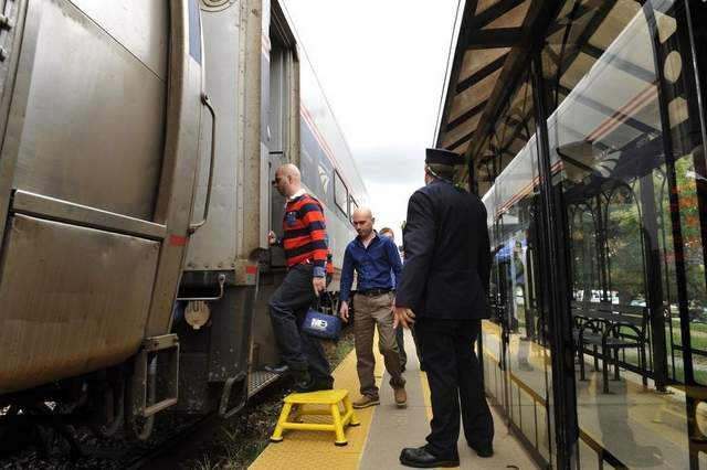 Passengers at the Royal Oak station board an Amtrak train bound for Chicago Friday afternoon. Michigan transportation officials hope faster service and on-time scheduling build ridership. (John T. Greilick / The Detroit News)
