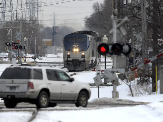 A vehicle crosses rail tracks in Royal Oak despite flashing warning lights. Train fatalities involving cars and pedestrians were up nationwide in 2014.(Photo: Todd McInturf / The Detroit News)